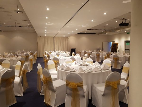 Room of white chaircovers with gold ties